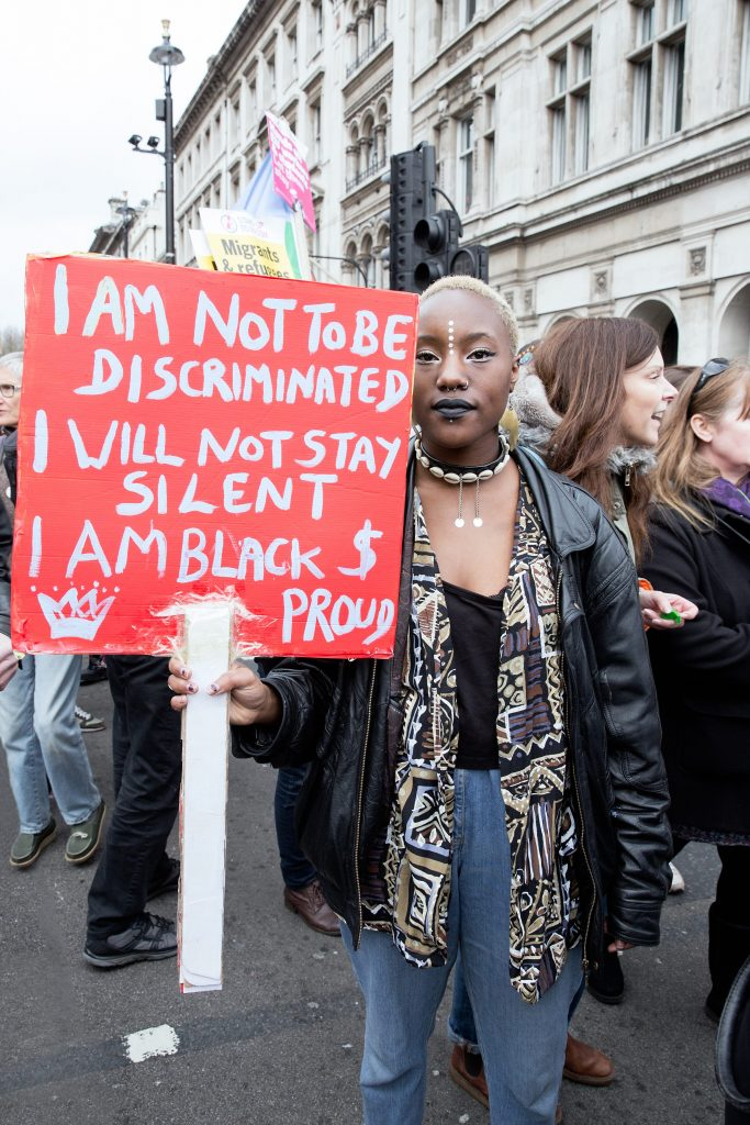 An anti-racism protester holding a sign saying: I am not to be discriminated, I will not stay silent, I am black and proud.