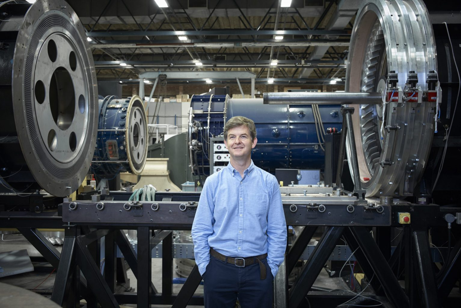 Professor Rob Miller standing in front of engine
